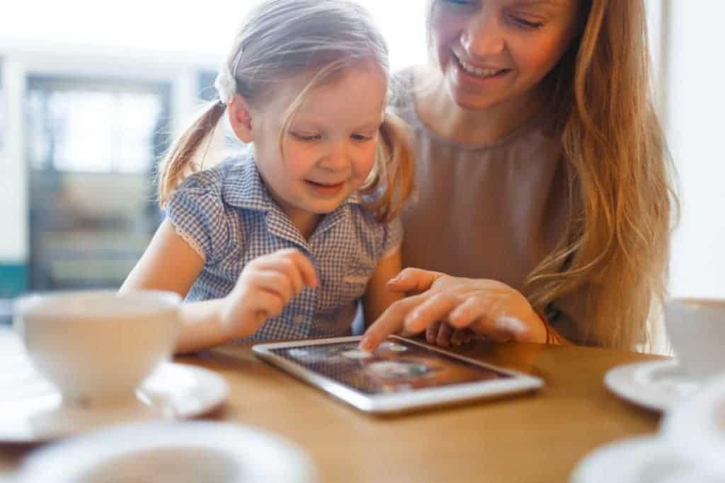 Madre enseñándole a su hija a usar una pantalla táctil