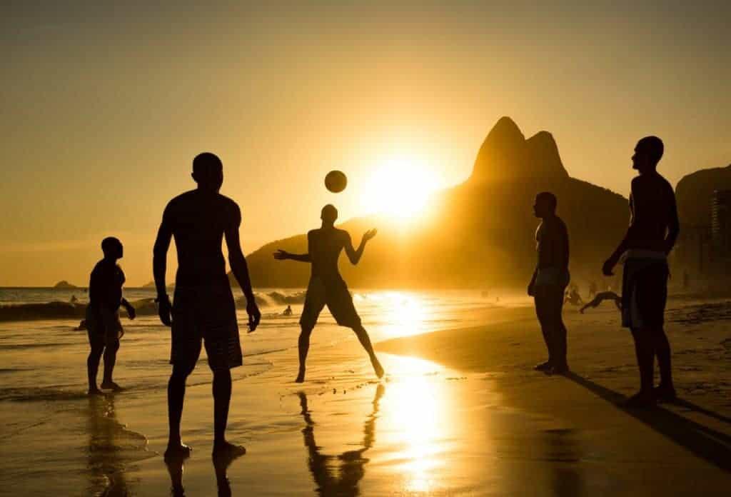 Silueta de locales jugando pelota en playa de Ipanema, Brasil