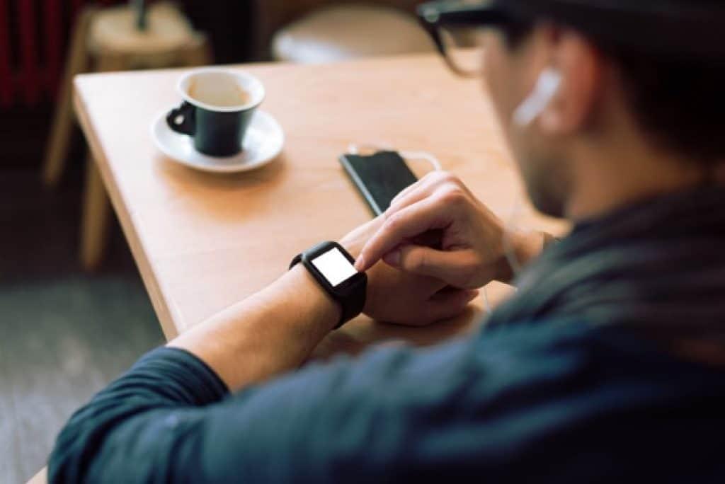 Hombre revisando reloj inteligente en un café bar