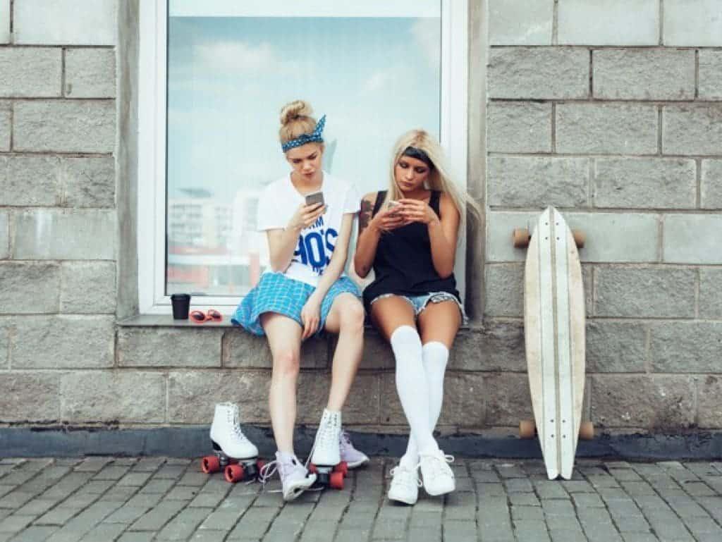 Dos amigas usando sus teléfonos inteligentes en exteriores