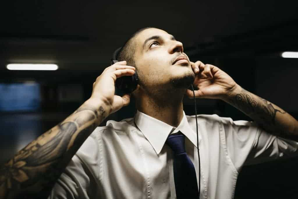 Joven empresario con tatuajes y audífonos en estacionamiento