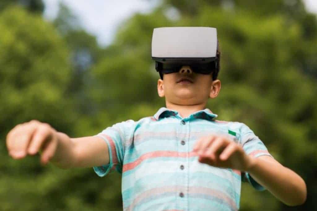 Niño con casco de realidad virtual en exteriores