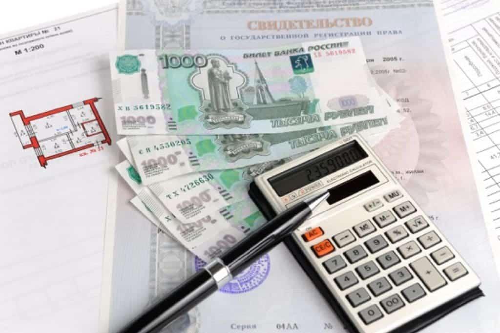 Dinero, calculadora, lapicera, título de propiedad y plan de pago de apartamento