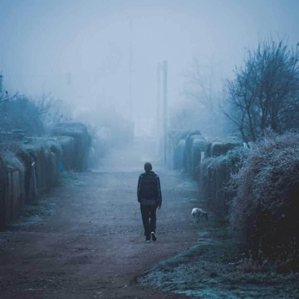 Paisaje nublado oscuro con hombre de espaldas