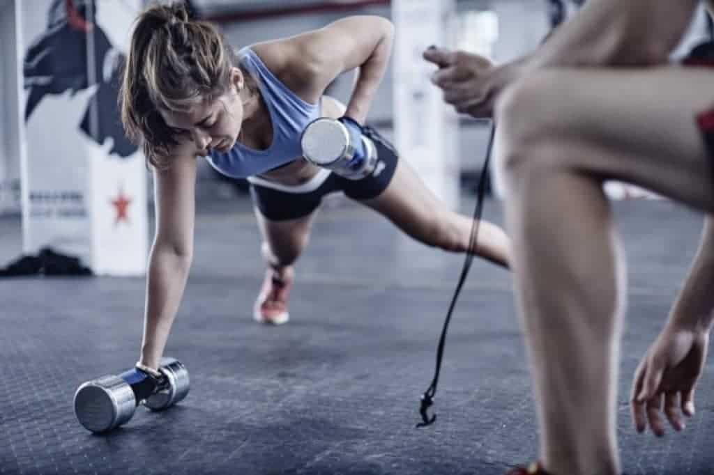 Entrenador de fitness tomando tiempo a mujer haciendo flexiones con pesas
