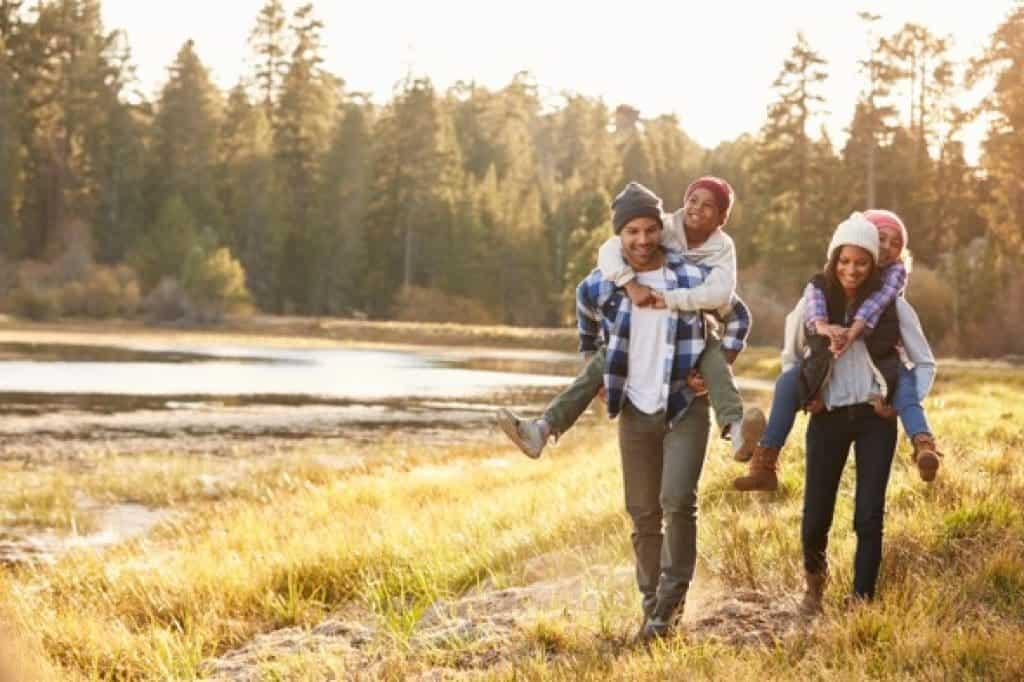 Padres cargando niños a la espalda en caminata junto al lago