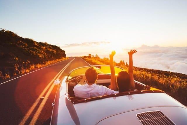 Pareja Conduciendo Convertible Atardecer