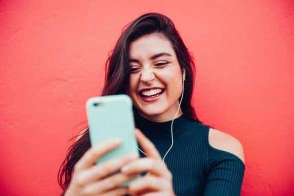 Adolescente sonriendo mientras mira el teléfono con los auriculares puestos