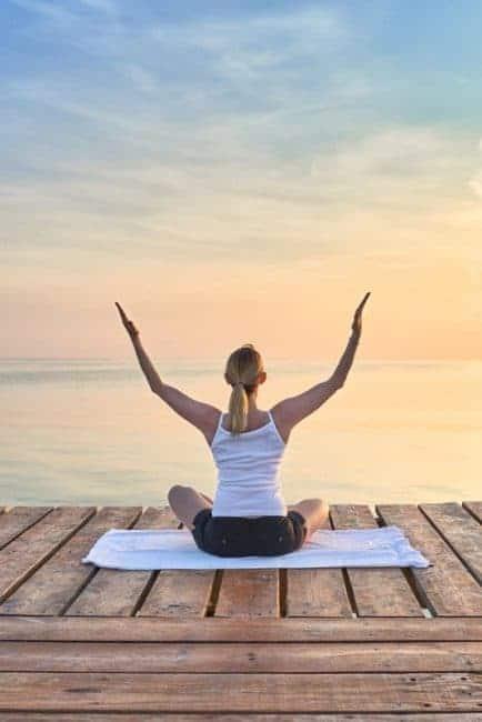 Mujer joven practicando yoga frente al mar