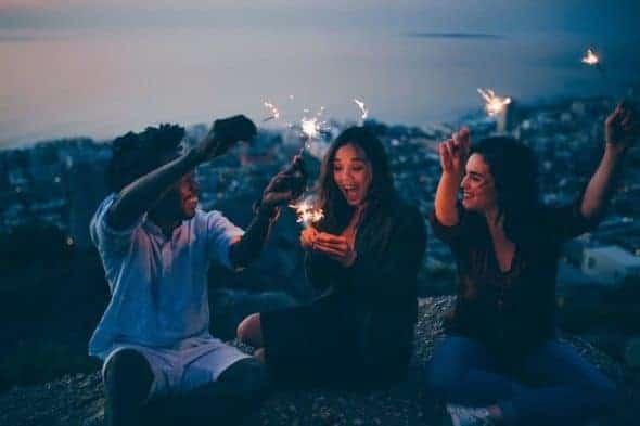 Grupo de amigas celabrando la noche en una roca con bengalas