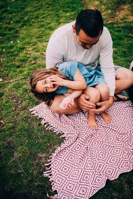 Padre e hija juegan sonrientes sentados en una manta en la hierba mientras la niña mira a la camara