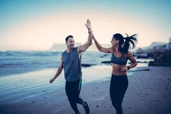Un hombre y una mujer chocan los cinco sonriendo mientras corren