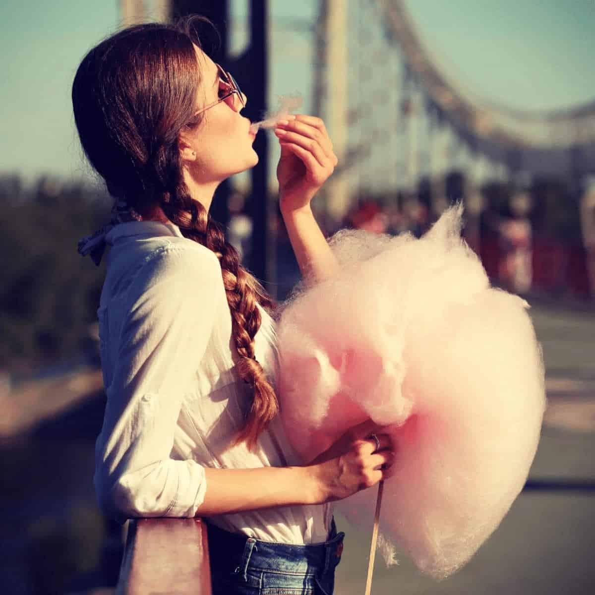 Mujer joven hipster comiendo algodon de azucar en un puente