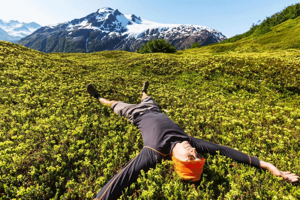 Mochilero relajandose tubando encima de una montaña