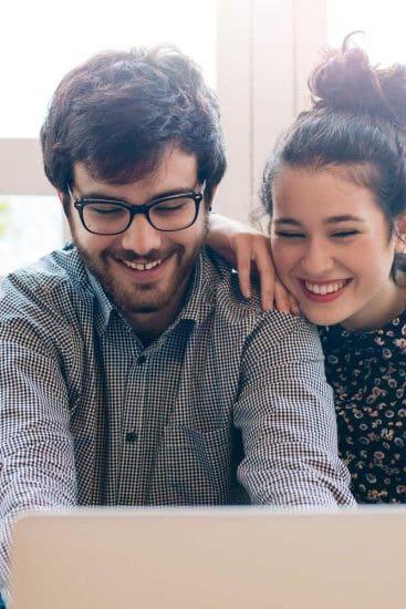 Pareja hispana hombre y mujer sonriendo delante del portátil